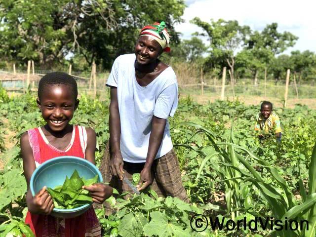 """""""후원자님 덕분에 이제 텃밭에서 수확한 채소들로 아이들에게 영양가 있는 음식을 해줄 수 있게 되었어요."""" -채리티(46세)년 사진"""