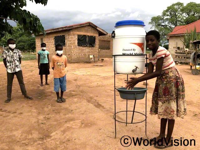 """""""후원자님 덕분에 마을에 간이 세면대가 생겼어요. 이제는 손을 비누로 깨끗이 씻어서 바이러스 감염을 예방해요."""" -레지나(11살)년 사진"""