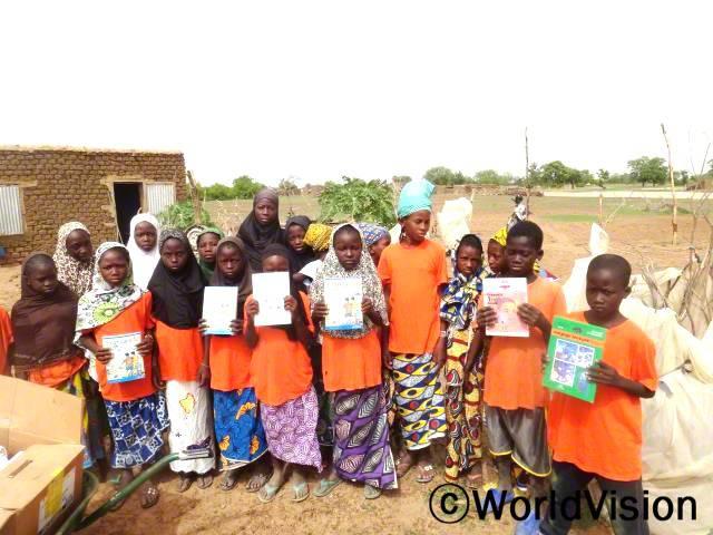 저는 읽기 실력에 도움이 되는 책을 받게 되어 너무 행복해요. 선생님들은 읽기 실력이 더 늘어야 하는 학생들을 위해 책을 가져다 주세요. -마두가(13세, 가장 오른쪽에 있는 아동)년 사진