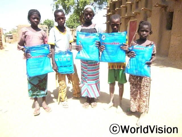 무사(11살, 왼쪽에서 두번째 흰 티셔츠를 입은 아동)와 그의 친구들은 말라리아 예방을 위한 모기장을 받고 감사했어요.년 사진