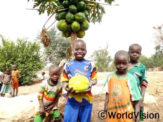 """""""저는 엄마와 함께 마을 공동텃밭에 가는 걸 좋아해요. 우리 마을 텃밭은 저 같이 어린 아이들에게 다양한 과일과 채소를 주기 위해 지어졌대요."""" -바카리(9세)년 사진"""