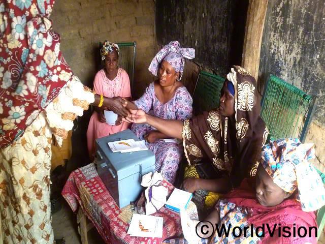 124명의 여성들이 모여 다섯 개의 마을 저축 그룹을 만들었어요. 이 그룹들은 돈을 저축하고 빌리는 데에 도움을 준답니다. - 아세투, 마을 저축 그룹 총무(갈색 두건 착용)년 사진