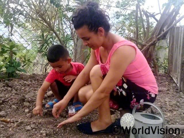 두니아가 작은 아들 린드로에게 야채텃밭에 식물을 심기전 땅을 고르는 법을 가르쳐 주고 있습니다.