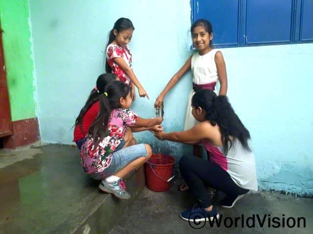 """아이들은 월드비전의 도움으로 손을 깨끗이 씻는 법과 손 씻기의 중요성에 대해 배웠어요. """"월드비전의 도움으로 손 씻는 법을 배운 덕분에 저희는 위생습관을 길러 건강하게 지내고 있답니다."""" -누리아 가브리엘라 (12세, 흰색 드레스를 입은 아동)년 사진"""