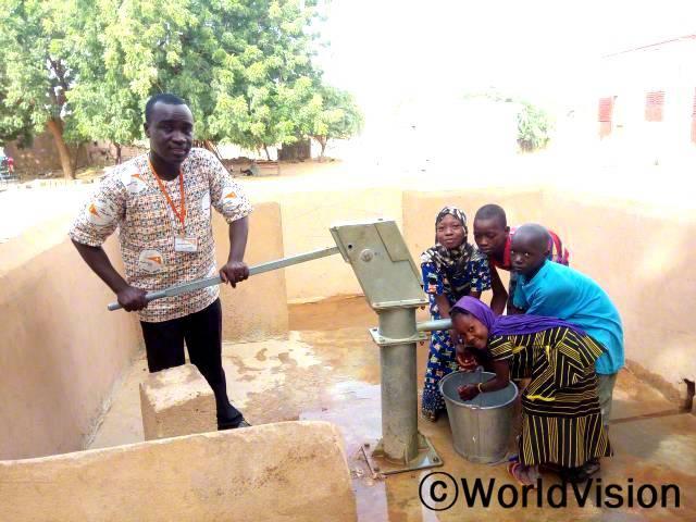 예전에 우리 학교는 물이 없었어요. 그런데 지금은 학교에 우물이 새로 지어져서 물을 마음껏 마실 수 있어요. 나디아, 9살 (앞쪽, 노란색,검정색)년 사진