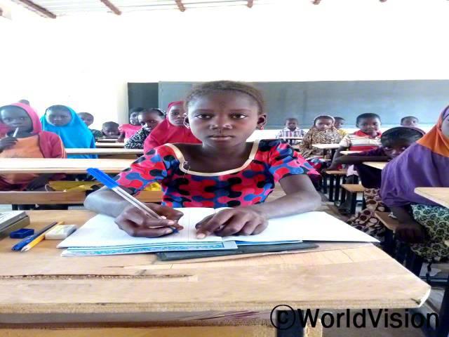 작년에 우리는 헛간에서 매트를 깔고 수업을 받았어요. 월드비전의 지원을 받고 난 지금은 학교 교실에서 공부해요. 마리아마, 10살 (앞쪽)년 사진