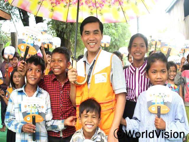 캄보디아 상큼트머이 지역개발사업장 팀장 속산 킨이 아동들과 함께 있는 사진입니다.년 사진