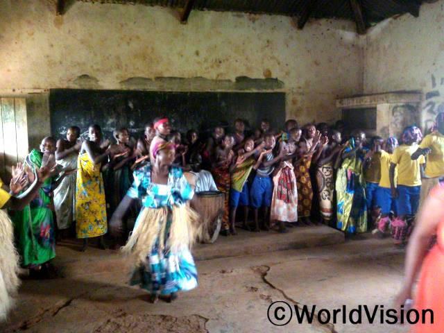 아이들은 음악, 춤 그리고 연극을 통해 아이들을 전염으로부터 보호하는 메시지를 듣습니다.년 사진