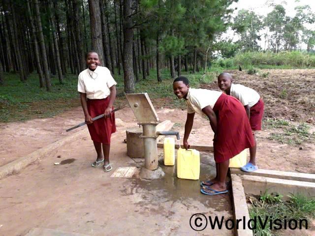 """월드비전은 안전하고 깨끗한 식수를 제공하기 위해 마을에 수도시설을 설치하였습니다. """"저희는 수도시설을 이용해 깨끗한 물을 마실 수 있어요."""" –세비카리(14세, 맨 왼쪽)년 사진"""