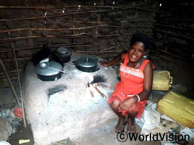 """월드비전은 마을주민들을 대상으로 에너지 절약형 화덕 만드는 법을 교육했습니다. """"저는 지금 화덕을 이용해 음식을 데우는 중이에요."""" –도린(19세)년 사진"""
