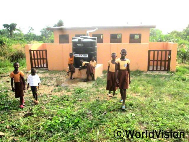 수도시설이 설치된 이후 위생환경이 발전했어요. 이제 저희 학교 학생들과 선생님들은 깨끗한 화장실을 사용해요. -아비바(12세), 오른쪽 첫 번째 아동년 사진