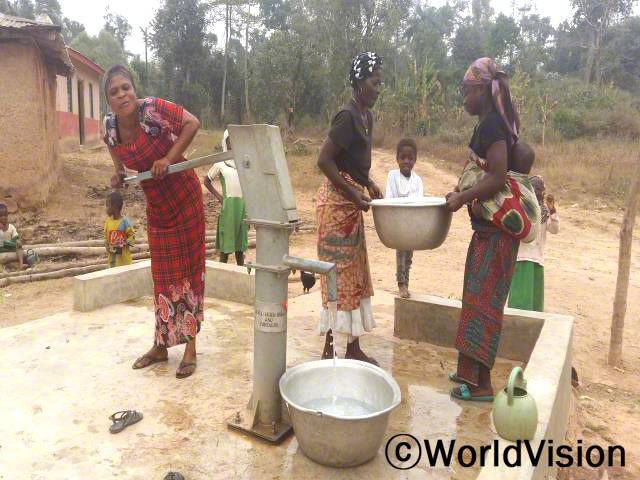 아쿠아(왼쪽)와 지역 주민들은 집과 학교에서 가까운 곳에서 안전한 물을 사용할 수 있게 되었어요.년 사진