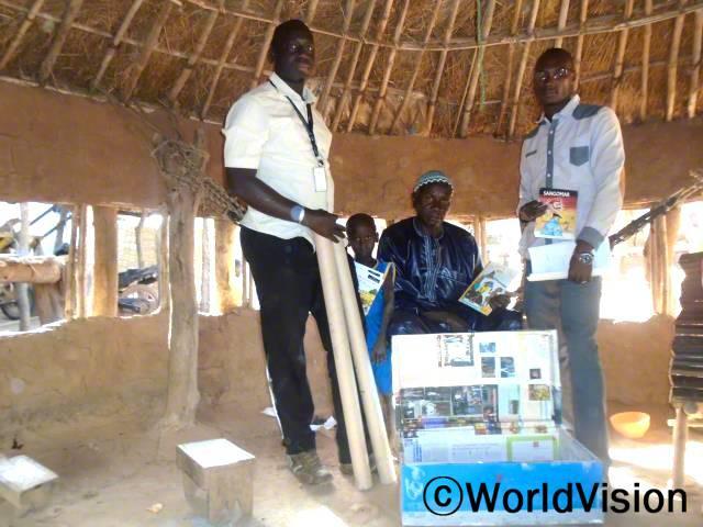 지역사회 보건 종사자들이 독서클럽을 위해 마을지도자에게 교육 자료를 기증하고 있습니다.년 사진