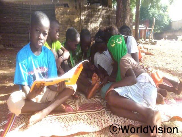 저희 학교 교실에는 책이 많지 않았어요. 저는 저희 마을의 읽기클럽에서 책을 볼 수 있어요. 이제 저는 읽을 책이 많이 있어요. -아마두(11세,하늘색 티셔츠를 입은 아동)년 사진