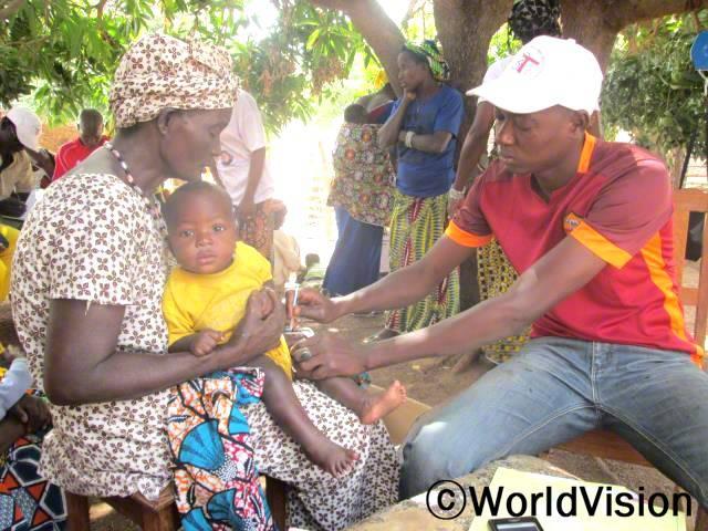 예전에는 여성들과 아동들의 건강을 후원하는 경우도 없고 신생아들도 예방주사를 다 맞지 않았어요. 지금은, 나이에 맞게 아이들이 백신을 맞아요. -디옵(수간호사, 빨간 셔츠를 입고 하얀 모자를 쓴 사람)년 사진