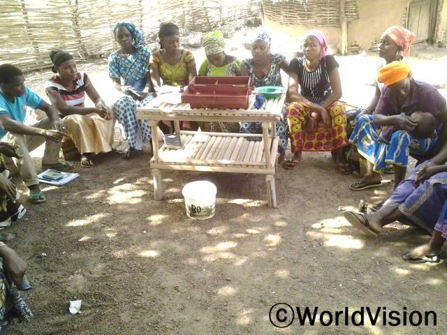 마을의 저축/대출그룹에 가입한 후로, 수입이 증가했어요. 마을에 어려움에 처한 많은 여성들이 이 그룹을 통해 도움을 받았어요. 그리고 저희는 가족들을 더 잘 돌볼 수 있게 되었어요.-코움바, 엄마(검정색 티셔츠,분홍색 스카프)년 사진