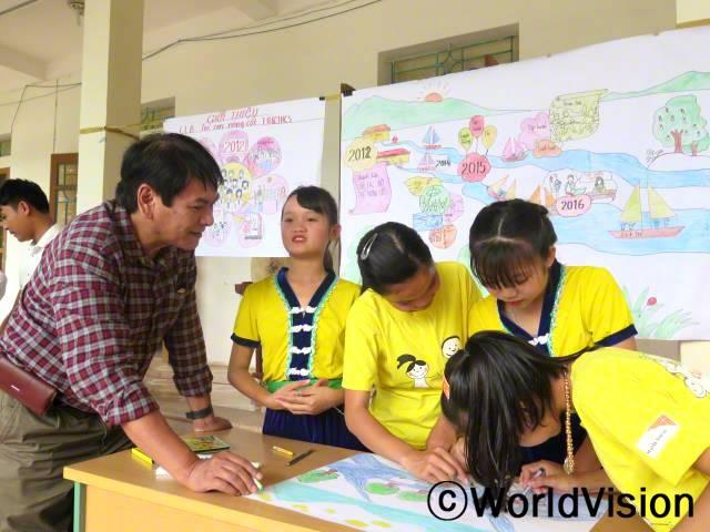 베트남 옌뚜이 지역개발사업장 팀장 하이 레 쿠앙 씨와 지역사회 아동들의 모습입니다.년 사진