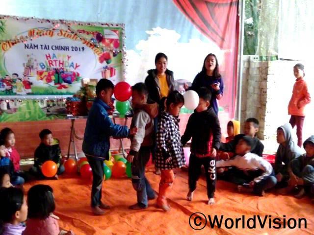 생일파티에 가는 게 너무 좋아요! 이야기도 듣고, 게임도 하고, 정말 재미있어요! - 티엔(6세, 풍선 게임을 하는 파란 점퍼 입은 아동)정기적으로 진행되는 생일축하파티는 아동 활동과 결합하여 진행합니다. 아이들은 즐거운 시간을 보내면서, 함께 배웁니다.년 사진