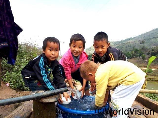 """""""전에는 물을 길으러 먼 길을 걸어가야 했는데 이제는 마을에 수도시설이 생겨서 언제든지 깨끗한 물을 쓸 수 있게 되었어요."""" –헝(8세, 맨 왼쪽)년 사진"""