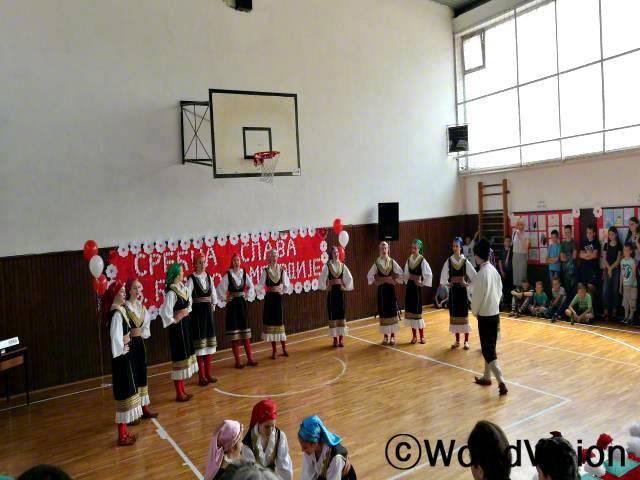 학교의 수호성인인 성 키릴루스와 성 메토디우스 축일을 맞이하여 9학년 학생들이 부모님들과 가족, 관람객들 앞에서 전통 노래에 맞춰 포크댄스를 추고 있습니다.