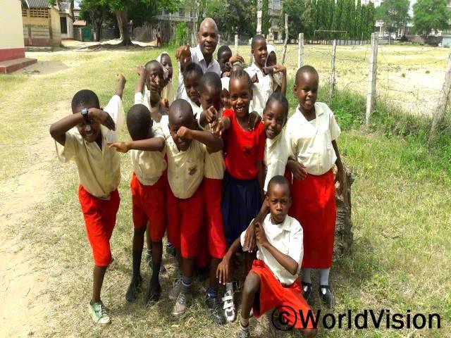 케냐 찬감웨 지역개발사업장 팀장 알렉슨 음와시 씨와 지역사회 아동들입니다.년 사진