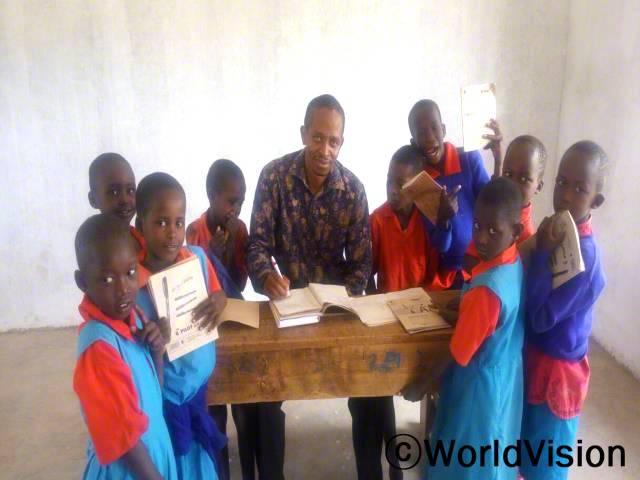 케냐 올도니로 지역개발사업장 팀장인 깁슨 키마니 씨가 올도니로 아동들과 함께 있는 모습입니다.년 사진