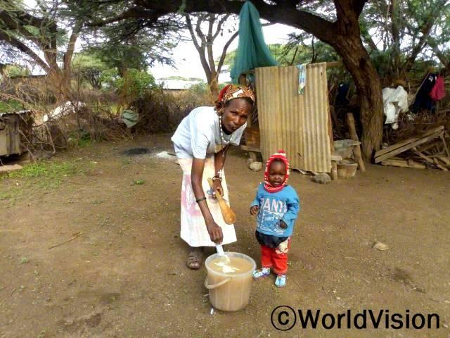 오쿠롬(왼쪽)이 아이에게 주기 전에 우물에서 뜬 물을 정수하고 있어요.년 사진