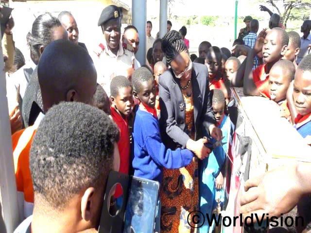 로메리오(13세, 7학년)가 아프리카 어린이의 날에 진행 한 식수 사업 오프닝에서 지역구위원과 함께 가위를 들고 있습니다.년 사진