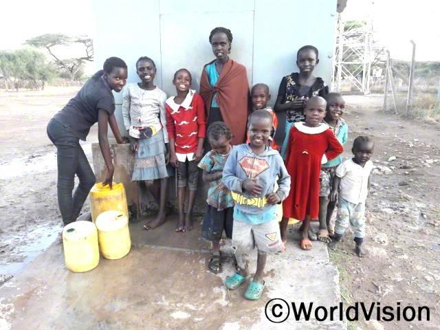 """""""월드비전의 도움으로 마을에 수도시설이 생긴 덕분에 깨끗한 물을 이용할 수 있게 되었어요. 이제는 물을 길으러 먼 길을 걸어가지 않아도 돼서 공부할 시간이 많이 생겼답니다."""" –에키도르(16세)년 사진"""