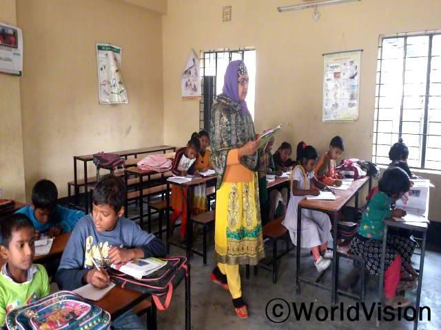 이제 우리 교실에 책상과 의자가 생겨 학생들은 공부에 더욱 집중할 수 있어요. 이전엔 바닥에 앉아 공부해서 제대로 배우기가 힘들었어요. -포리다(선생님, 서 있는 사람)년 사진