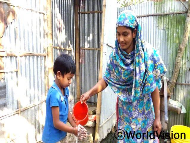 뷰티(엄마)는 화장실 앞에서 아들 사고르(왼쪽)의 손 씻는 것을 도와주고 있어요.년 사진
