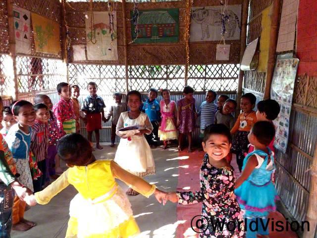 유치원이 저희 집 근처에 있어요. 친구들이랑 놀고 같이 읽고, 그리고 숫자를 배워요. -아나미카(5세), 가운데 하얀드레스를 입은 아동년 사진