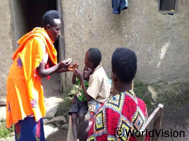 예전에는 보건소와 멀리 떨어진 곳에 살았기 때문에 말라리아, 설사병, 폐렴과 같은 질병이 어린 아동들의 목숨을 앗아갔어요. 이제 보건 관계자가 집에 방문하여 아동들을 치료해주고 있는 덕분에 아동들이 회복하고 있어요. -줄리엣(엄마, 서 있는 사람)년 사진