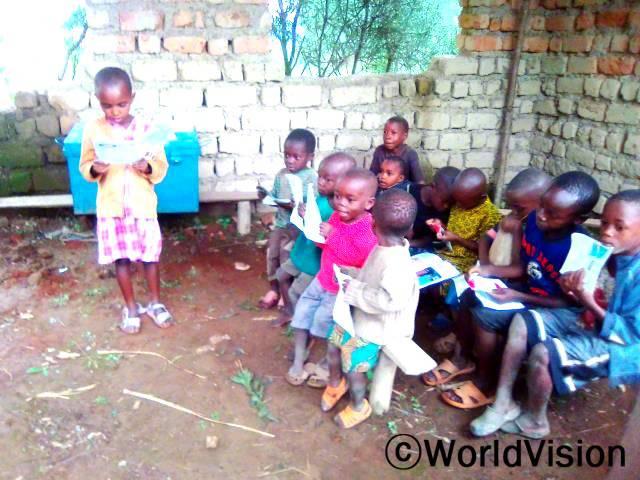 5살 때부터 마을 읽기 캠프에 다닌 덕분에 읽기와 쓰기를 배웠어요. 이제 저는 7살이고, 학교에서 읽기 캠프를 다니지 않은 친구들보다 더 잘하고 있어요. -시엘라(7세, 서 있는 아동)년 사진