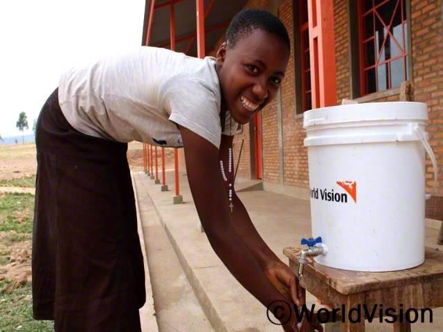 """""""월드비전의 도움으로 코로나19 예방 교육과 위생키트를 지원받아 학교에 들어가기 전에 항상 손을 깨끗이 씻어요. 저희는 친구들이나 마을 사람들에게도 코로나19 예방 수칙을 알려주고 있답니다."""" -파스칼린(17세, 학교 위생모임 회원)년 사진"""