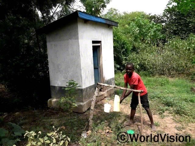 """월드비전은 마을에 간이 세면대를 설치하고 마을 주민들에게 위생교육을 실시했습니다. """"화장실을 다녀온 후에는 손을 깨끗이 씻어야 해요."""" –프란시스(12세)년 사진"""