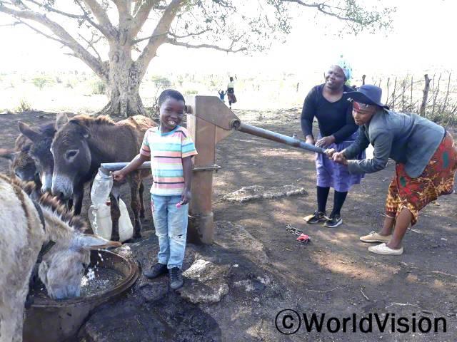 """""""월드비전의 도움으로 마을에 수도시설이 생겨서 이제 더 이상 물을 길으러 먼 길을 걸어가지 않아도 돼요. 덕분에 저희는 집 근처에서 안전하고 깨끗한 물을 마실 수 있게 되었답니다."""" –삼불로(5세)년 사진"""