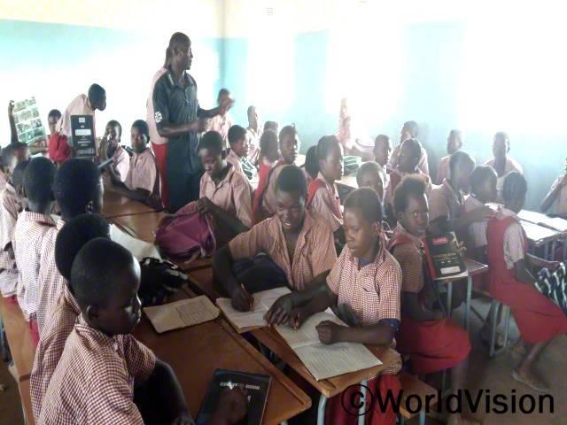 학교에 새로운 책상이 생기고 나서 아이들은 이제 더 이상 바닥에 앉아서 수업을 듣지 않아요. 지금은 개선된 교육환경을 갖게되었어요. -프리지에(선생님)년 사진