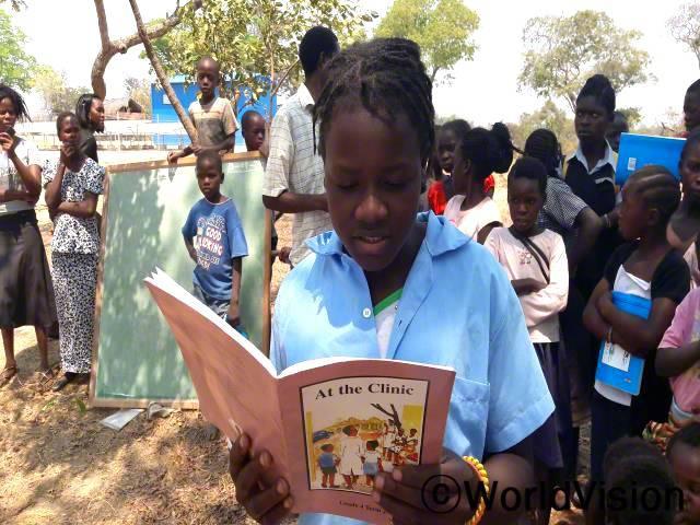 저는 독서 캠프를 통하여 더 잘 읽을 수 있게 되어 행복해요. 이제 우리 마을에는 독서자료들이 더 많이 생겼어요. -레베카(9세, 책 읽는 아동)년 사진