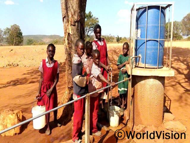 새로운 우물과 수도시설이 학교에 생긴 후 학생들이 더는 깨끗한 물을 길으러 먼 길을 가지 않아도 돼요. 우리는 너무 행복해요. 어서 작은 정원을 만들고 싶어요. -신시아(8세, 양동이를 들고 있는 아동)년 사진