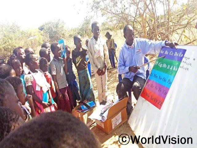 독서 캠프 강사(막대기를 들고 있는) 브라이언은 그의 마을에서 독서 캠프를 통해 아이들을 가르칠 수 있어서 행복합니다.년 사진
