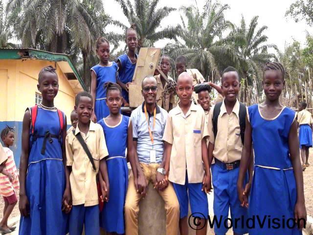 시에라리온 소로베마 지역개발사업장 팀장 셰쿠 맘부씨와 지역사회 아동들의 모습입니다.년 사진