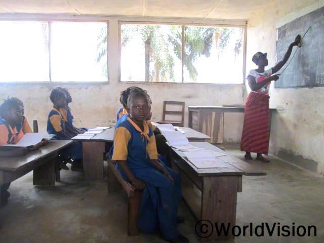 예전에 저희 선생님은 저희를 가르칠 훈련을 받지 못하셨었어요. 이제 선생님이 새로운 교수법을 배우셨고, 저희가 더 쉽게 공부할 수 있게 되었어요. -마미(7세, 카메라를 보고 있는 아동)년 사진