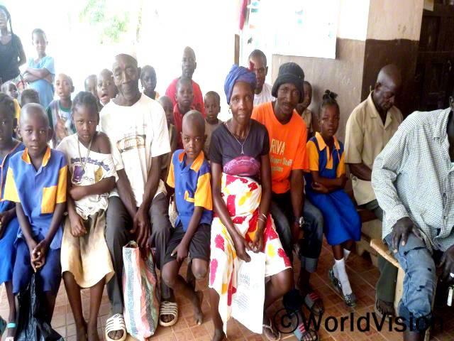 파(흰색 상의를 입고 흰색 모자를 쓴 남성)씨는 자신의 마을사람들이 더이상 미신을 믿지 않고, 아동 교육의 장점을 알게 되어 기뻐요.년 사진