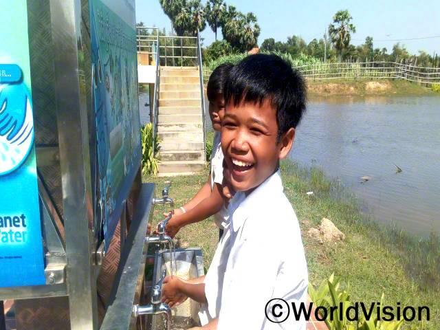학교에 정수기가 설치되어서 이제 친구들과 깨끗한 물을 사용할 수 있게 되었어요. 예전과 달리, 정수된 물을 마실 수 있게 되어서 설사병에 걸리지 않아요. -피룸(11세, 앞에 있는 아동)년 사진