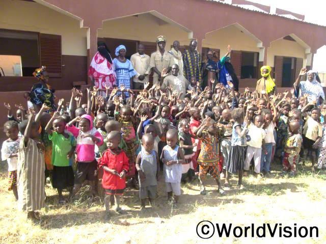 새 유치원이 지어질 수 있도록 지원해 주셔서 감사해요. 300명의 학생들에게 안전하게 공부할 공간이 생겼어요. -세쿠(학교 행정직원, 중앙에 손을 들고 있는 사람)년 사진
