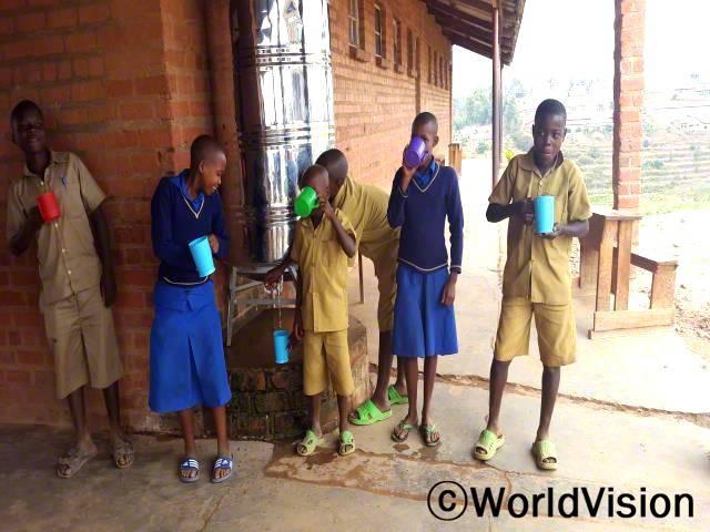 저는 우리에게 이제 물 필터가 생겨서 너무 행복해요. 이전에 저희는 물이 더러워 물을 마실 수 없었어요. 이제 우리 학교에 깨끗한 물이 생겼고, 우리는 더 건강해졌어요. -조세핀(14세, 맨 왼쪽)년 사진