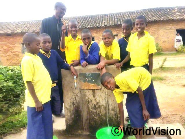 학교에 수돗가가 생겨서 너무 기뻐요. 더 이상 교실을 청소하기 위해 개울로 물을 길으러 갈 필요가 없어요. 공부할 시간도 더 생기고 학교 성적도 더 올랐어요. -안젤리크(13세, 녹색 대야를 만지고 있는 학생)년 사진