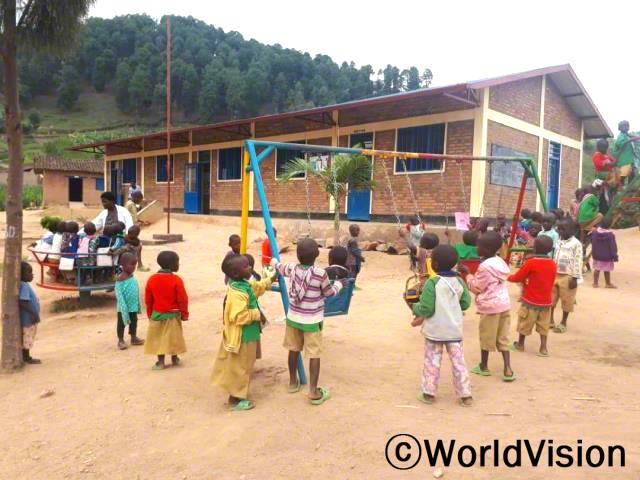"""""""학교에 놀이터와 놀이시설이 설치됐습니다. 아이들은 이곳에서 공놀이도 하고, 미끄럼틀도 타고, 그네도 타며 즐겁게 놉니다.""""- 임마누엘(지역개발사업장 팀장)년 사진"""