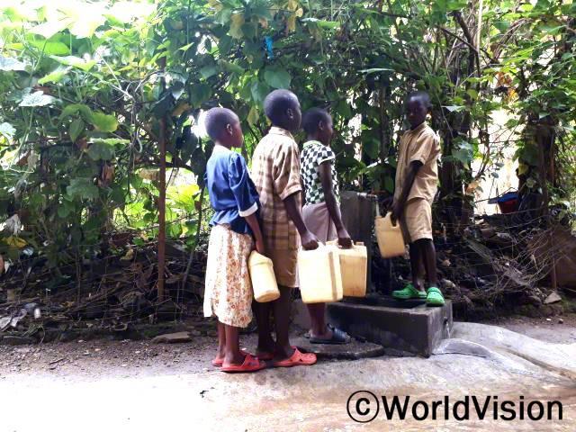 """""""이제 학교에서도 물을 사용할 수 있어요. 요즘에는 일주일에 2-3일 정도 교실 대청소도 해요. 덕분에 깨끗한 환경에서 공부하고 있지요. 이제 물 때문에 아플 일이 전혀 없어요."""" -베르틴(올라가 서 있는 아동)년 사진"""